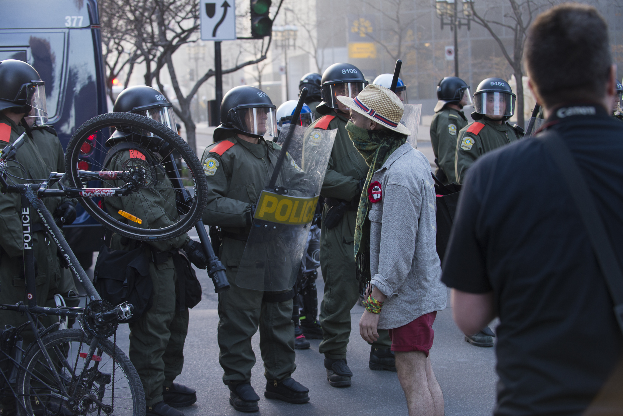 A final protester stands in defiance as riot police yell at him to back off because he is too close.- A.I.