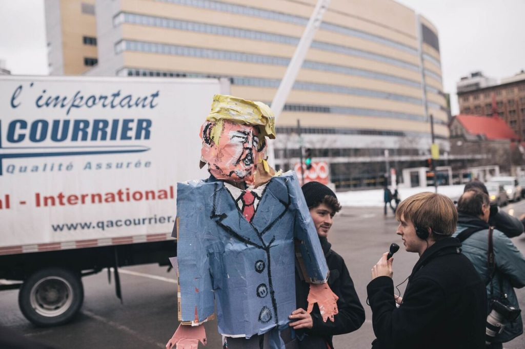 Journalist Ian Down interviewing protester Jonathan Ouzariman, who made paper-mâché effigy of President Trump. Photo by Kirubel Mehari.