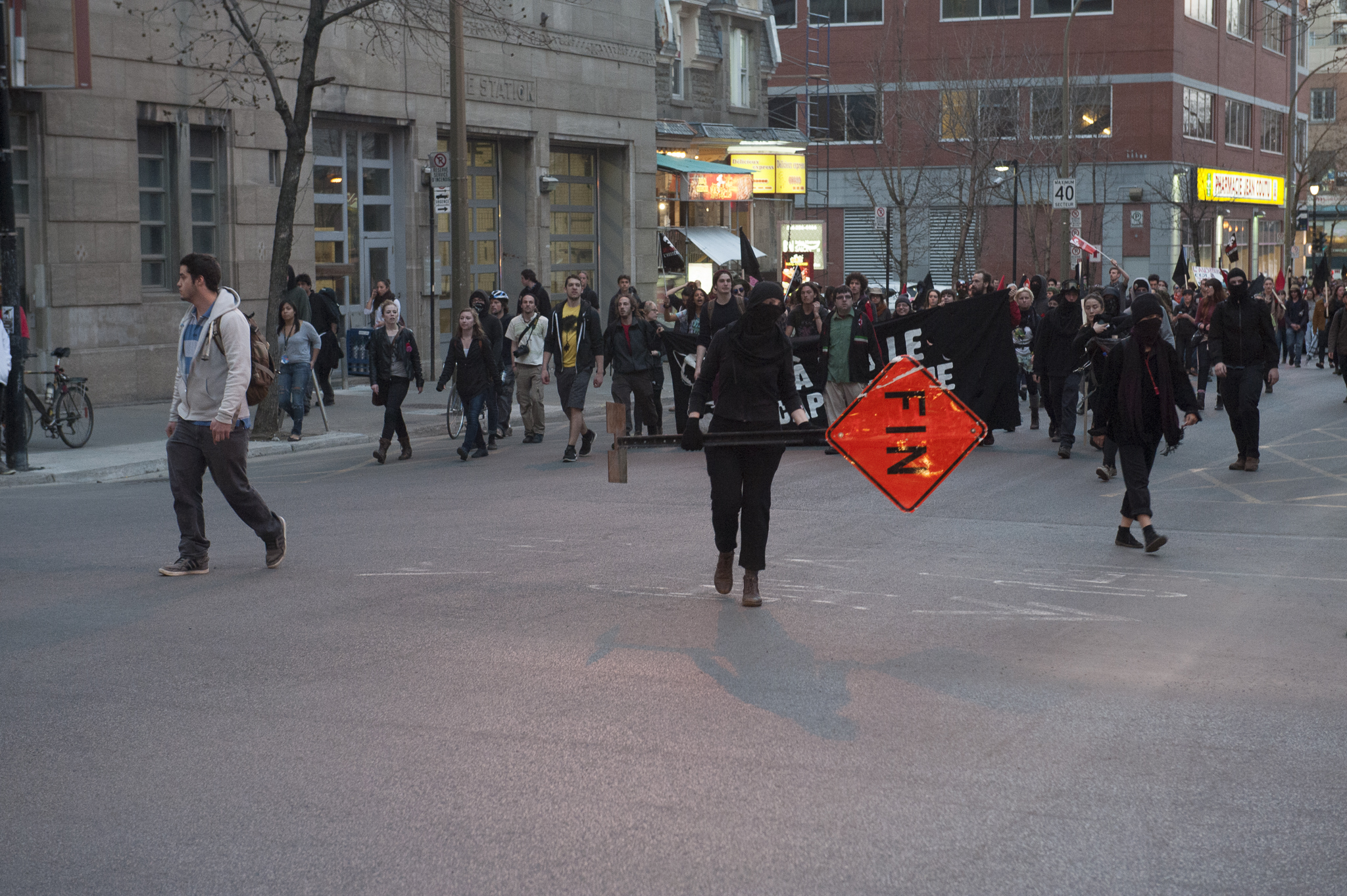 Masked protesters use road signs to block traffic on Maisonneuve St. - A.i.