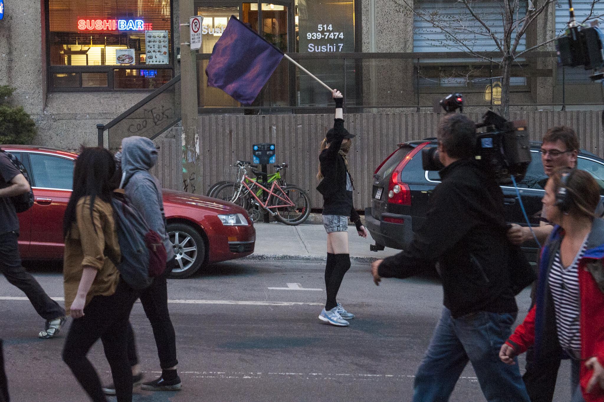 A masked protester waves a black flag on St-Mathieu St. - A.I.