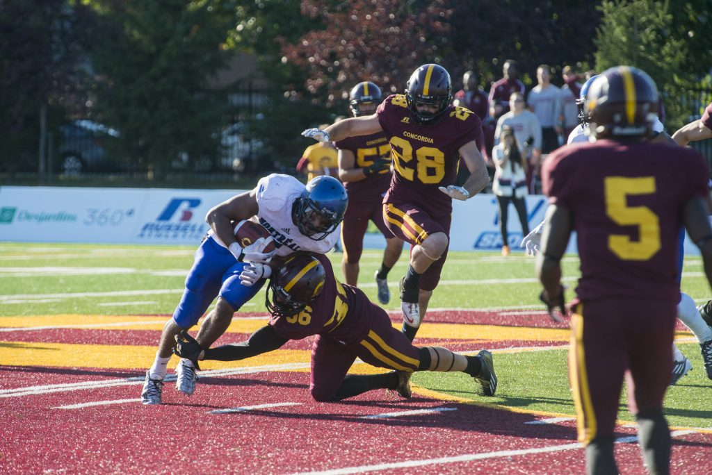Third year defensive back Mikael Charland lunging for the tackle. Photo by Andrej Ivanov.