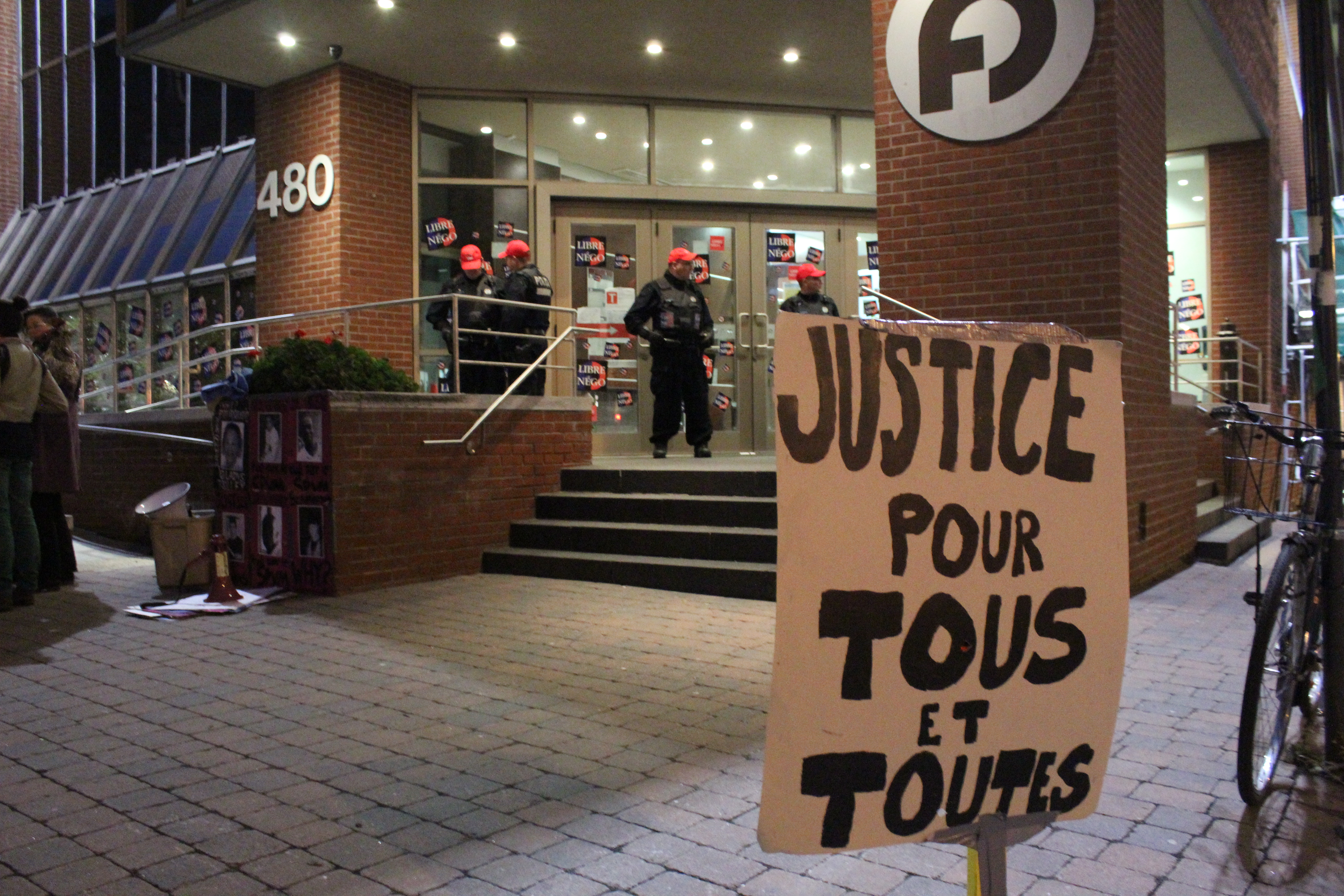 Police watch on as family and friends of victims of police killings gather for an annual vigil outside of the Fraternité des policiers et policières de Montréal office.  Photo by Gregory Todaro.