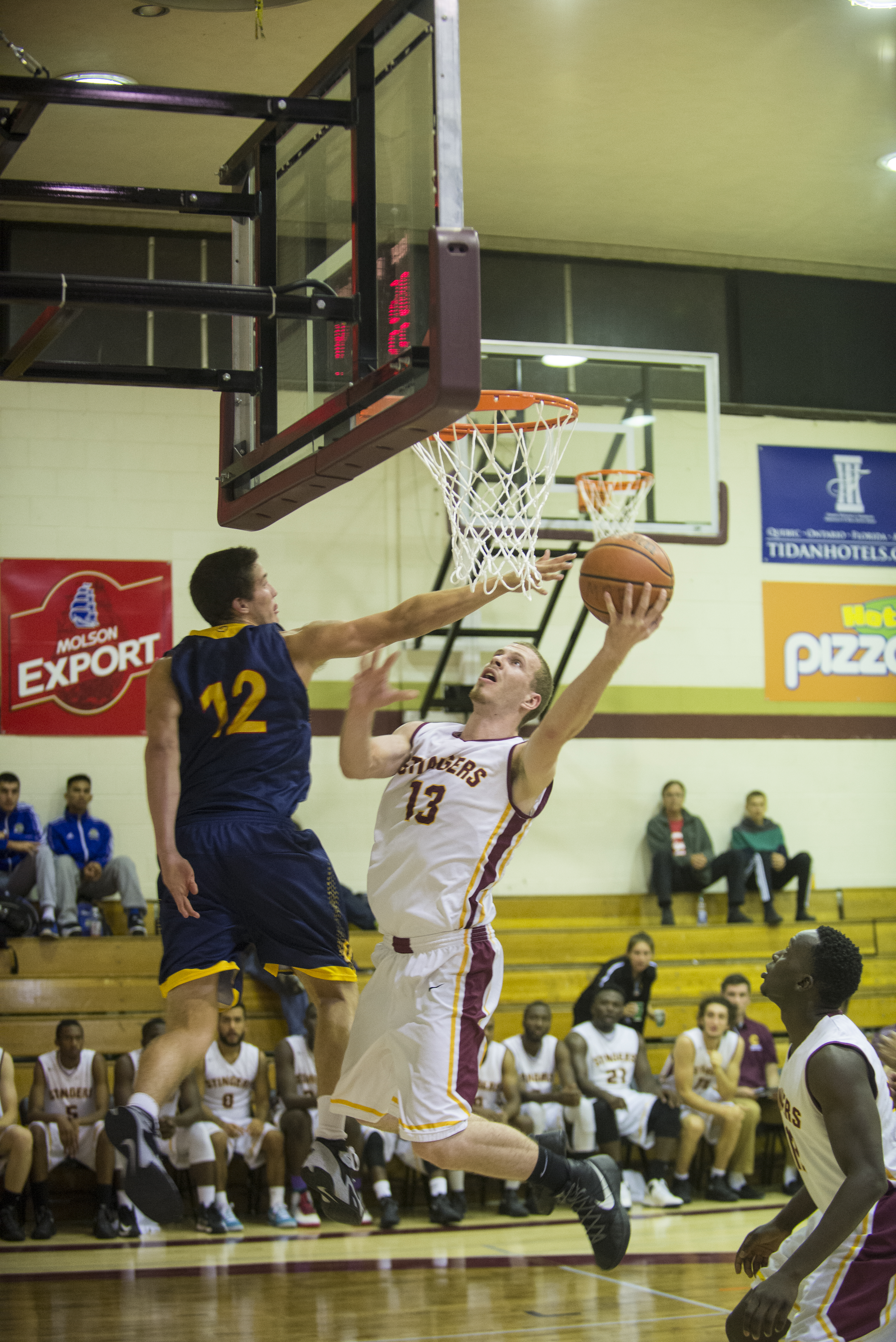 Concordia's Ken Beaulieu goes up for the layup on the Queen's defender. Photo by Andrej Ivanov.