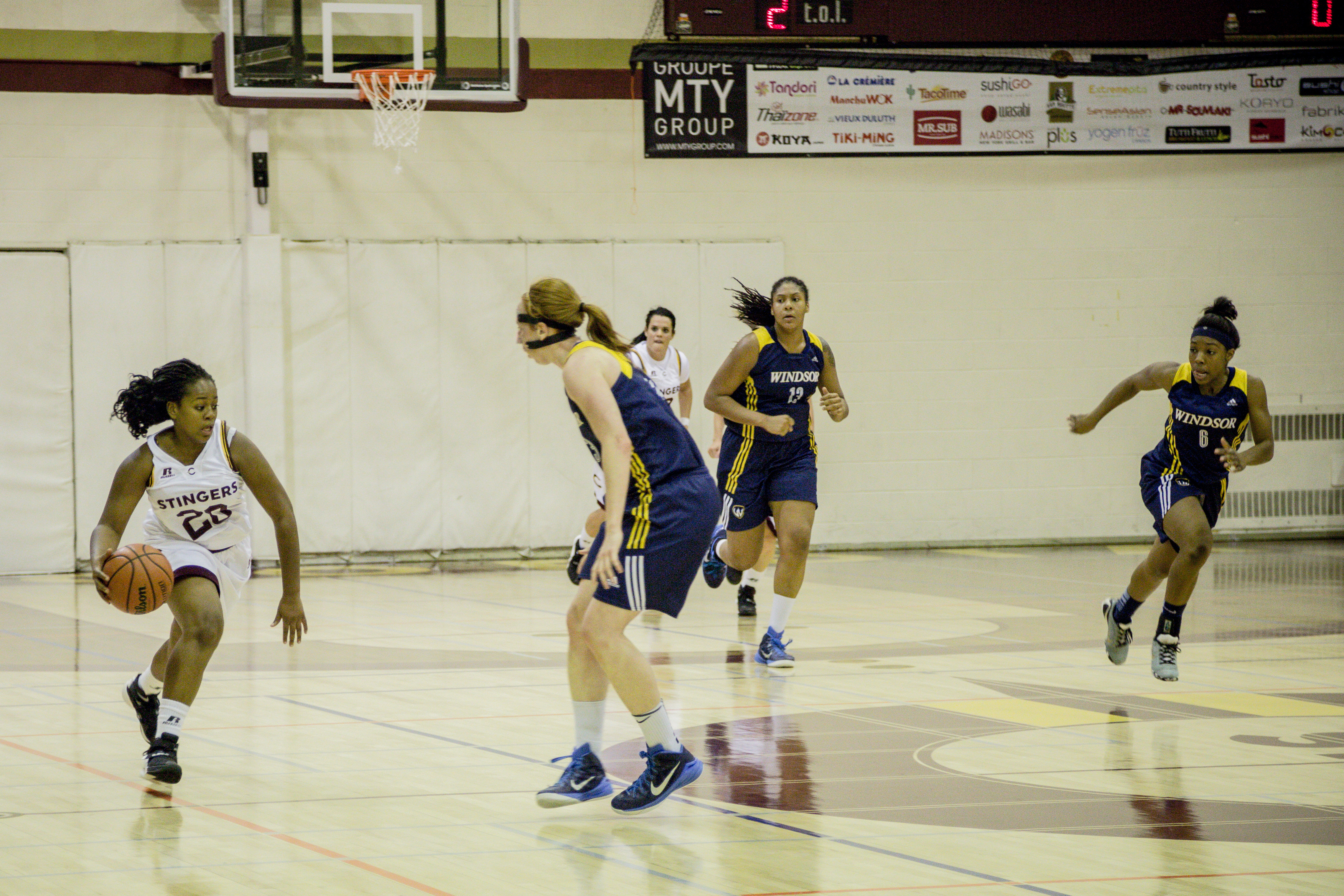 Stingers guard Latifah Roach dribbling up the court against their Windsor Lancer Opponents in Friday's game at Loyola. Photo by Marie-Pierre Savard.