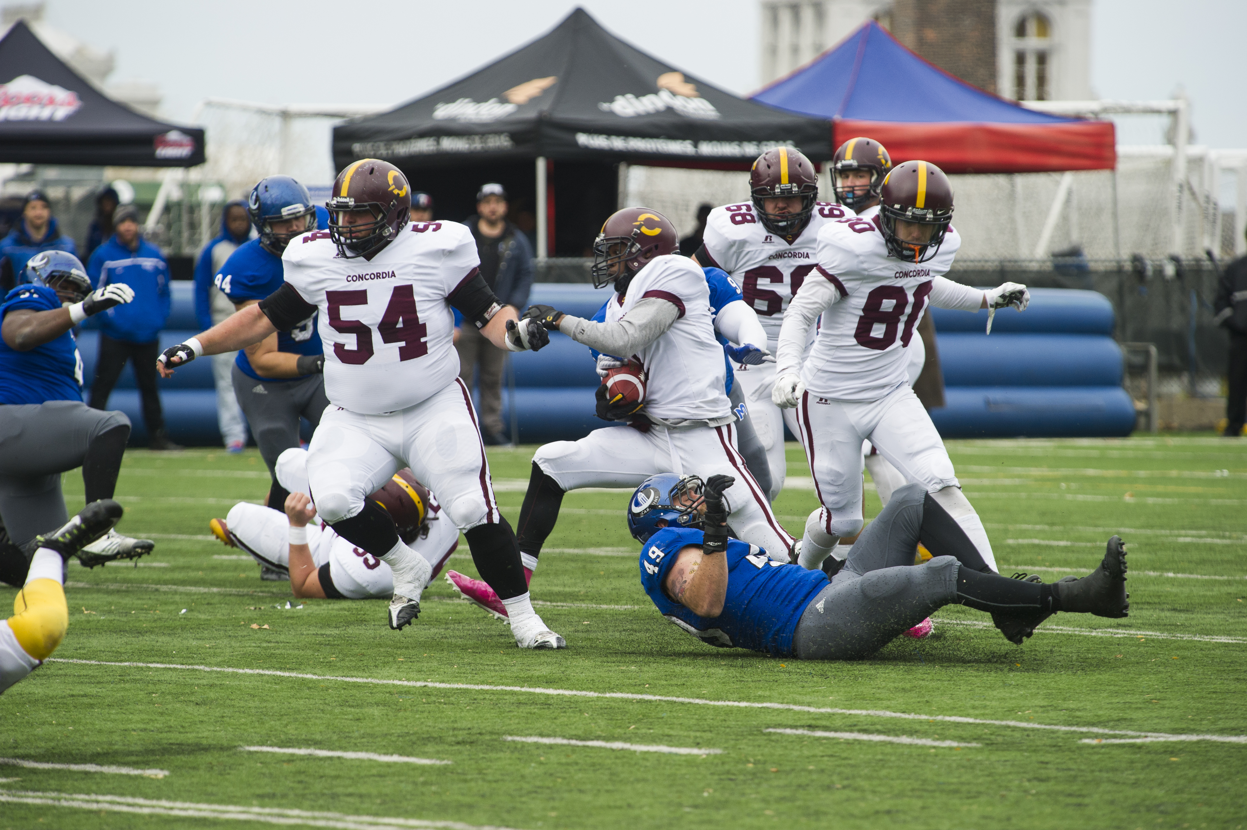 Stingers players clear the way for Jean-Guy Rimpel as he runs the ball. Photo by Andrej Ivanov.